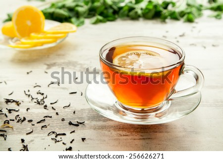 Glass cup of tea on a wooden table with sliced lemon. - stock photo