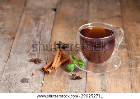 Glass cup of tea with cinnamon sticks on wooden table background.  - stock photo