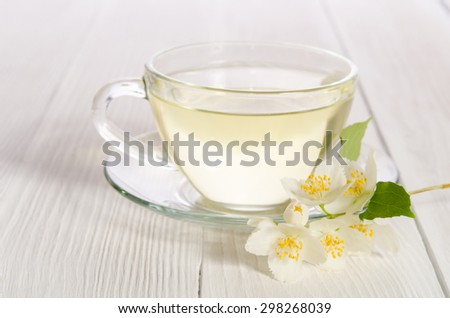 Glass cup of tea with jasmine on the white wooden background - stock photo