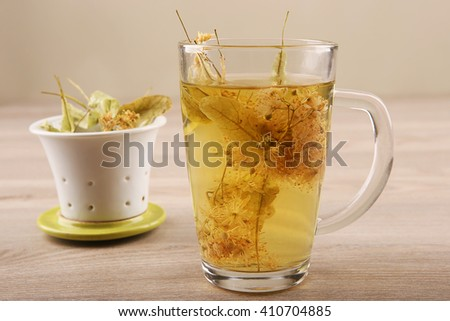 Glass cup of tea with lime dry blossom and strainer.. Linden decoction. - stock photo