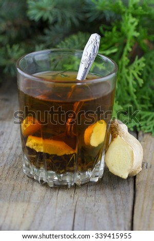 Glass cup of tea with mint and ginger, thuja branches on wooden background - stock photo