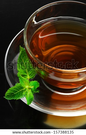 Glass cup of tea with mint on black background. - stock photo