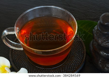 glass cup of tea with wet zen stones  - stock photo