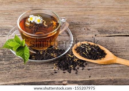 Glass Cup Tea with camomile flower and Mint Leaf, on brown wooden palette