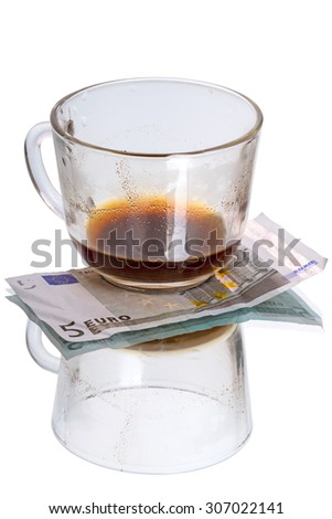 Glass cup with coffee residues and five euro isolated on white background - stock photo