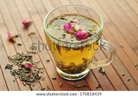 Glass cup with fresh green tea and dry roses  - stock photo