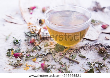 Glass cup with hot tea on the white birch bark and dry pink roses and green leaves - stock photo