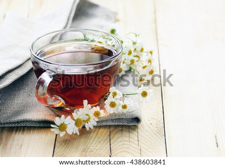 glass cup with tea and chamomile on a wooden background - stock photo
