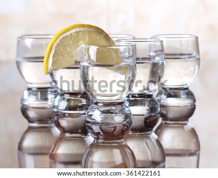 Glass cup with tequila and lemon on table    - stock photo