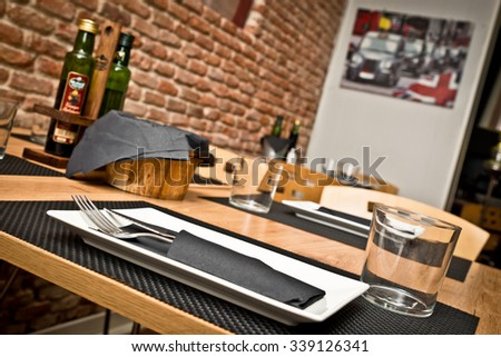 Glass, cutlery and dish on an modern restaurant table with brick wall