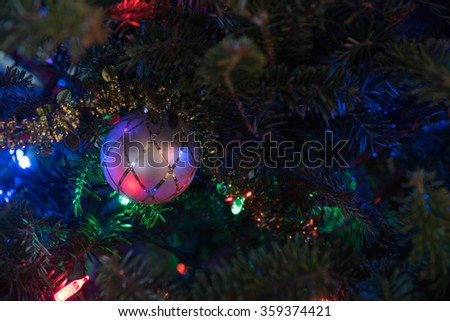 Glass decorations on christmas tree lighted up by holiday garland - stock photo