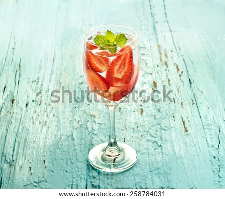glass delicious refreshing drink of strawberry and apple with mint on blue wooden background, infusioned water, soft focus and vintage color tone - stock photo