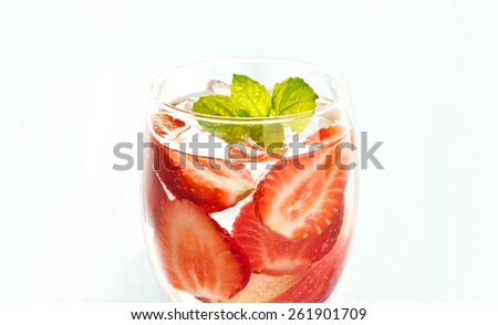 glass delicious refreshing drink of strawberry and apple with mint on on white background, infusioned water, warm color tone - stock photo