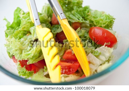 Glass dish with fresh salad and food tong - stock photo