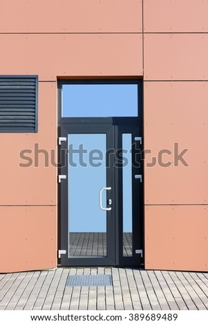 Glass door of new  no name red office in the modern mass production  building. The sky and pavement is reflected in glass - stock photo