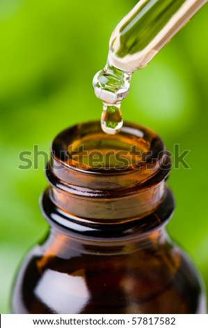 Glass dropper filled with herbal essence, aromatherapy oil, homeopathic medicine, or other liquid. - stock photo