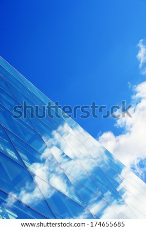 Glass facade reflecting blue sky with clouds