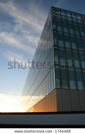 Glass faced building below cirrus clouds at sunset - stock photo