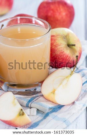 Glass filled with fresh Apple Juice on wooden background