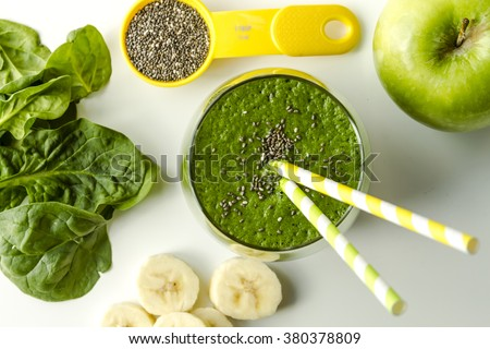 Glass filled with spinach and kale green detox smoothie with yellow and green swirled straws surrounded by raw ingredients in yellow spoons - stock photo