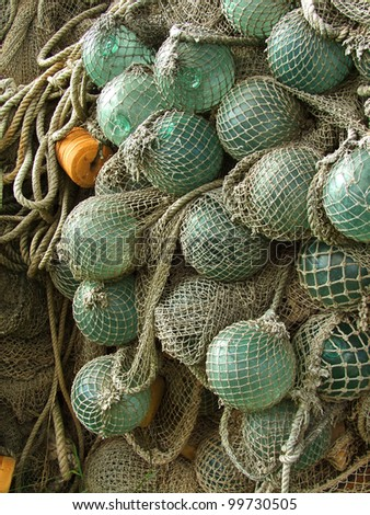 glass float, old fishing nets - stock photo