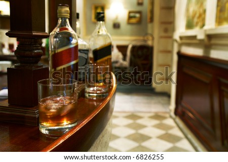 Glass from whiskey and a bottle on a table at restaurant - stock photo