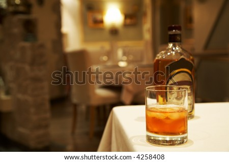 Glass from whisky and a bottle on a table at restaurant - stock photo