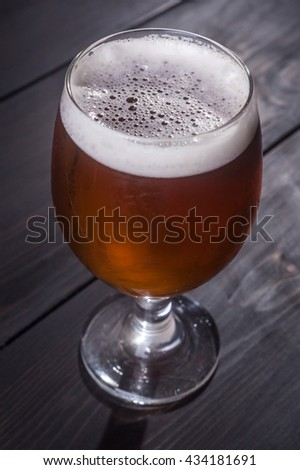 Glass full of amber ale on a dark wooden table - stock photo