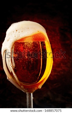 Glass full of beer with dark background - stock photo