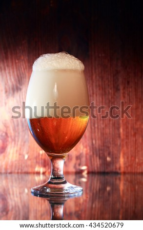 Glass full of beer with foam against wooden background - stock photo