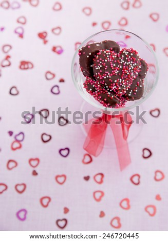 Glass full of chocolate heart cookies on a soft pink background - stock photo