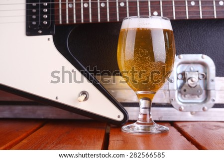 Glass full of light beer standing on a wooden table with a music equipment case and electric guitar in the background - stock photo