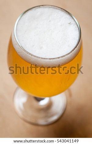 Glass full of light lager beer standing on a textured wooden table
