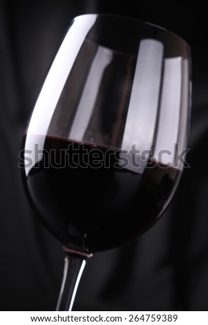 Glass full of red wine shot over a dark background