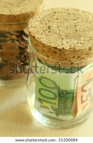 Glass Glass containers with coins and euro of a banknote - stock photo