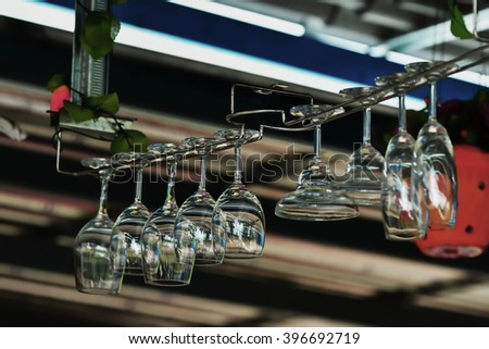 Glass glasses hanging above the bar rack