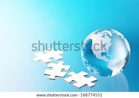 Glass globe and jigsaw puzzle pieces. Building global business.  - stock photo