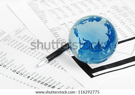 Glass globe and pen on finance - stock photo