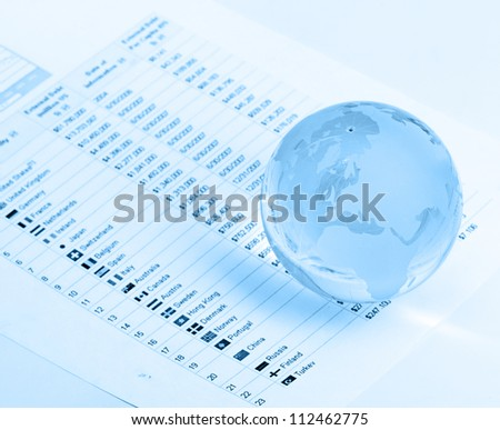 Glass globe and pen on finance background - stock photo
