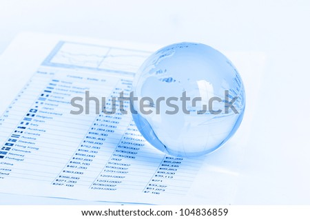 Glass globe and pen on finance chart - stock photo