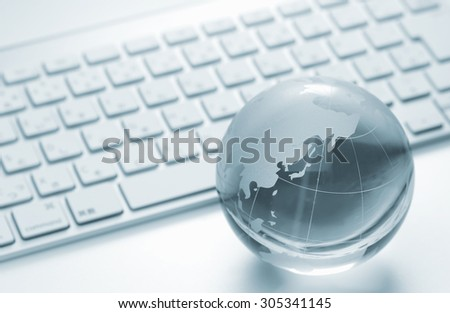 Glass globe and the keyboard - world business and economy - stock photo