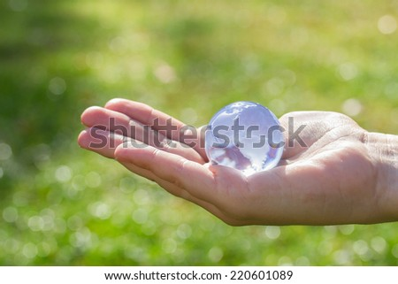 Glass globe in hand  in the grass concept for environment - stock photo
