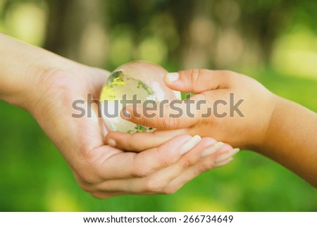 Glass globe in hands - stock photo