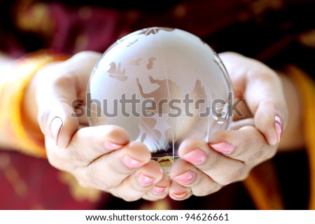 Glass globe in the hands - stock photo
