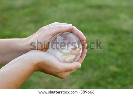 Glass Globe in Woman's Hands Outdoors - stock photo