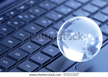 Glass globe lying on black laptop computer keyboard