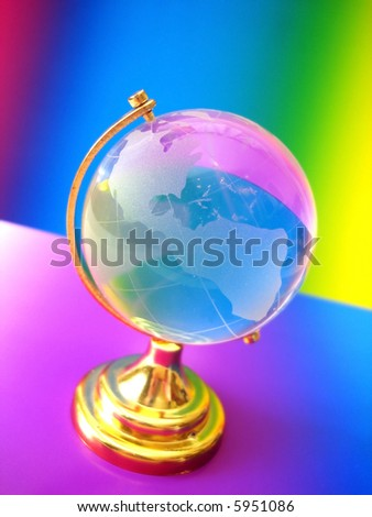 glass globe of the world on colored background - stock photo