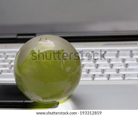 Glass globe on a laptop keyboard - stock photo