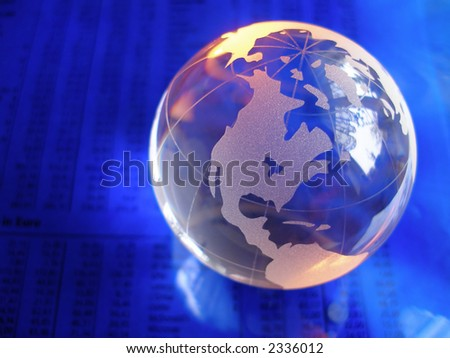 glass globe on blue stock market and financial figures with orange highlights