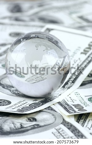 Glass globe on dollar bills pile. - stock photo